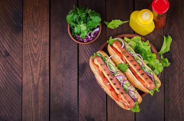 Hot dog con salchichas, pepino, tomate y lechuga en la mesa de madera oscura. perrito caliente de verano. vista superior
