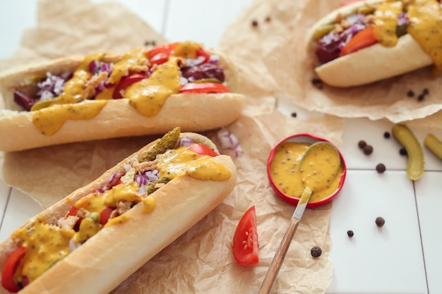 Hot dog con salsa sobre superficie blanca