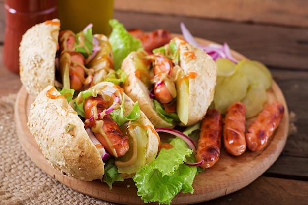 Hot dog - sandwich con pepinillos, cebolla roja y lechuga sobre fondo de madera