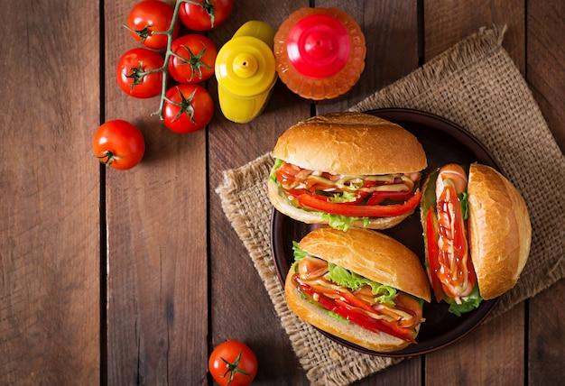 Hot dog - sandwich con pepinillos, pimentón y lechuga sobre fondo de madera. vista superior
