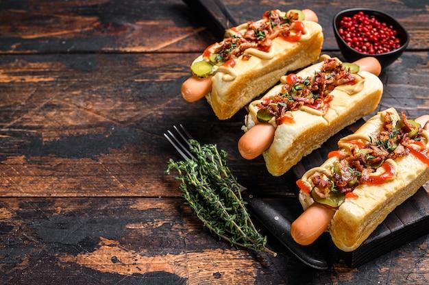 Hot dogs completamente cargados con tocino frito, cebolla y pepinos encurtidos. fondo de madera oscura. vista superior. copie el espacio.