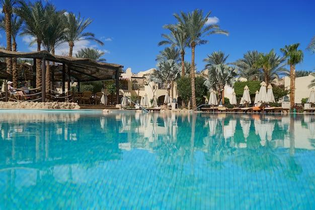 Hotel con palmeras y piscina en verano.