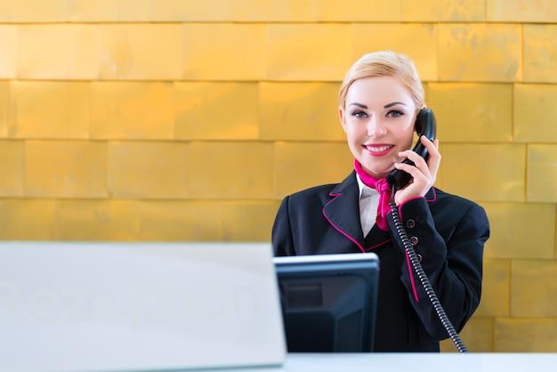 Hotel recepcionista con teléfono en recepción.