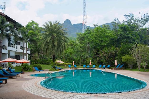 Hotel tailandés desierto con una piscina, palmeras y hamacas en un día soleado vista frontal