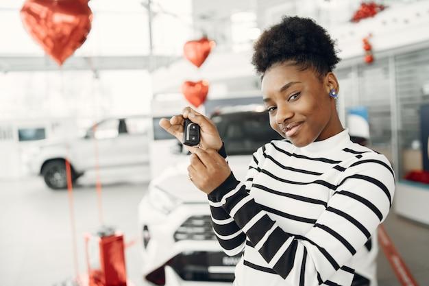 Hoy fui de compras. foto de una atractiva mujer africana muestra las claves de la cámara.
