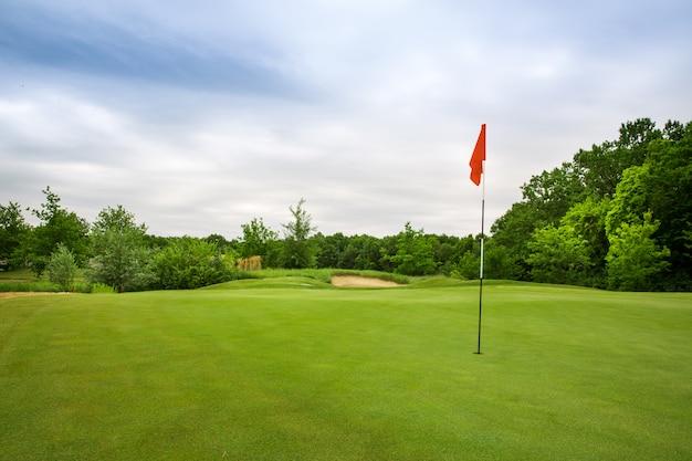 Hoyo final con bandera, césped en campo de golf