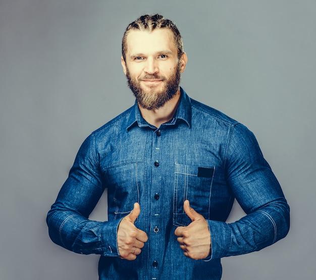 Hsome hombre barbudo en ropa casual apunta lejos, sonriendo