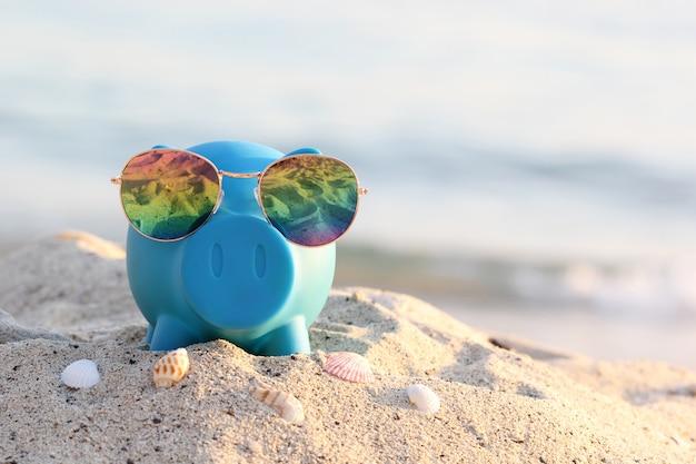 Hucha azul con gafas de sol en la playa del mar, ahorro de planificación para el presupuesto de viaje del concepto de vacaciones