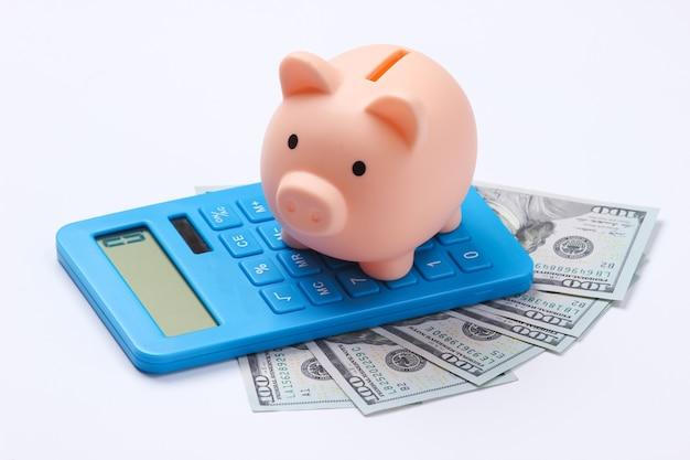 Hucha con billetes de 100 dólares y calculadora en blanco