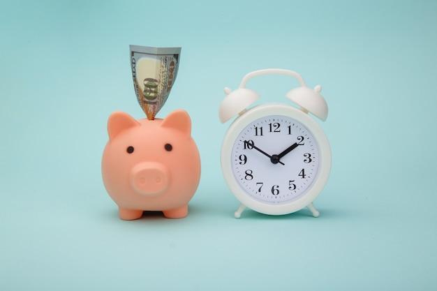Hucha con billetes de dinero y despertador sobre fondo azul. el tiempo es dinero concepto