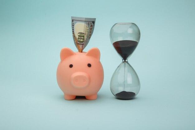 Hucha con billetes de dinero y reloj de arena en azul