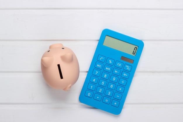 Hucha y calculadora azul sobre superficie de madera blanca. vista superior
