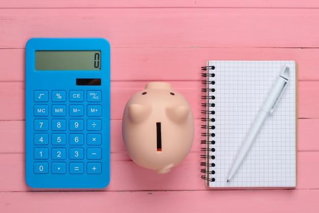 Hucha y calculadora, cuaderno sobre superficie de madera rosa. vista superior
