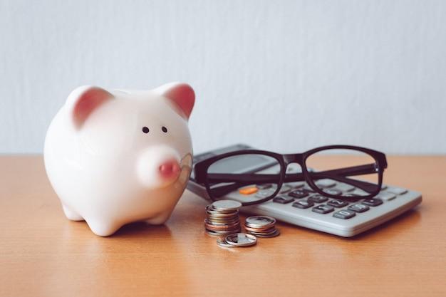 Hucha, calculadora y monedas en mesa de madera
