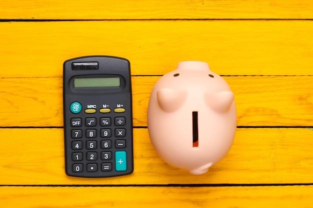 Hucha y calculadora sobre una superficie de madera amarilla. vista superior