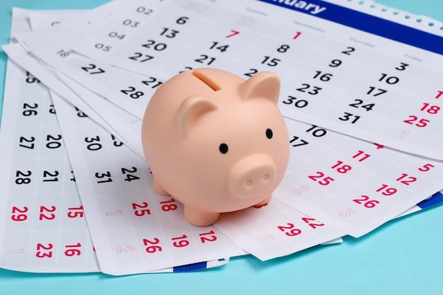 Hucha con un calendario mensual en azul. pago de alquiler de vivienda o préstamos.