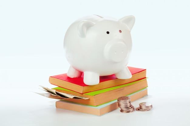 Hucha de cerámica con libros y dinero.