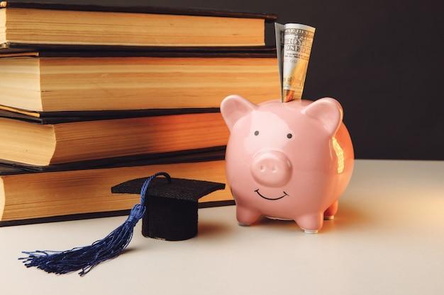 Hucha de cerámica con pila de libros y tapa. universidad, posgrado, concepto de educación.
