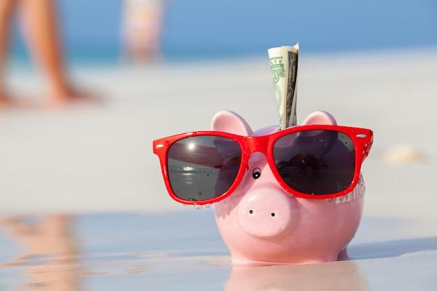 Hucha de cerdo rosa en gafas de sol rojas en la playa