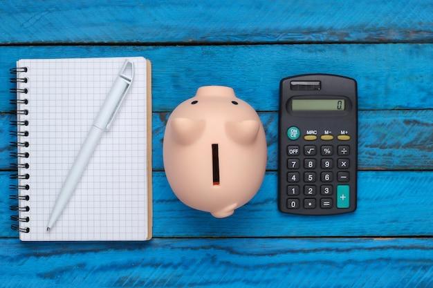 Hucha con cuaderno y calculadora sobre una superficie de madera azul. vista superior
