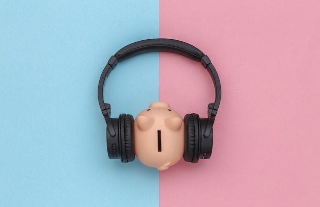 Hucha escucha auriculares estéreo sobre fondo azul-rosa pastel. vista superior