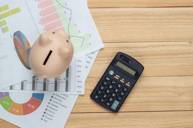 Hucha con gráficos y tablas, calculadora sobre tablas de madera. cálculo económico, estadísticas, costes. endecha plana. vista superior