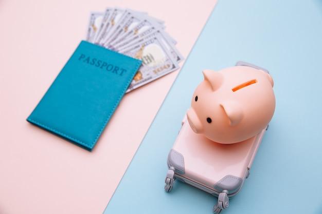 Hucha en maleta y pasaporte con dinero en superficie rosa azul. ahorre dinero para viajar