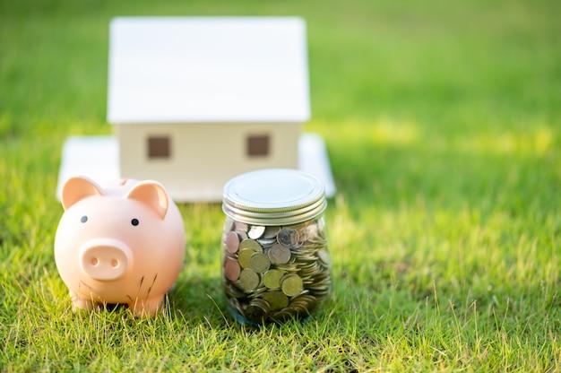 Hucha y un modelo de casa, concepto ahorro de dinero para la casa y los bienes raíces.