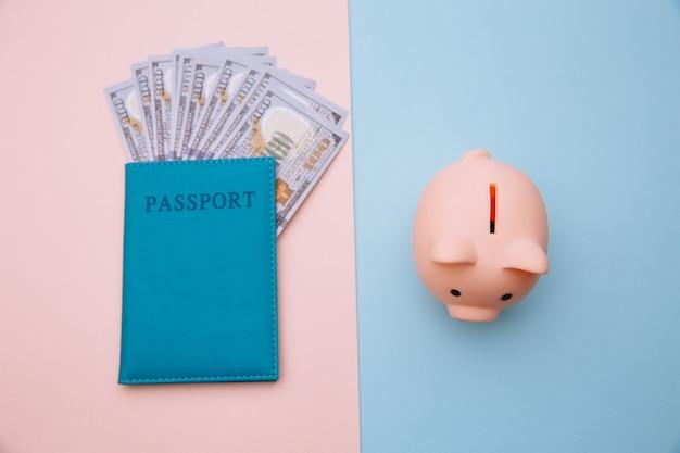 Hucha y pasaporte con dinero en superficie rosa azul. ahorre dinero para el viaje.