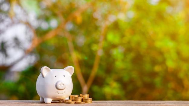 Hucha y una pila de monedas de oro en la mesa de madera vieja. - concepto de negocio y gestión. copyspace