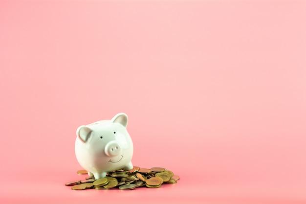Hucha y una pila de monedas de oro en rosa