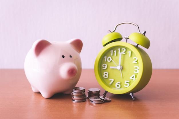 Hucha, reloj despertador y monedas. para negocios en crecimiento. tiempo para salvar el concepto.
