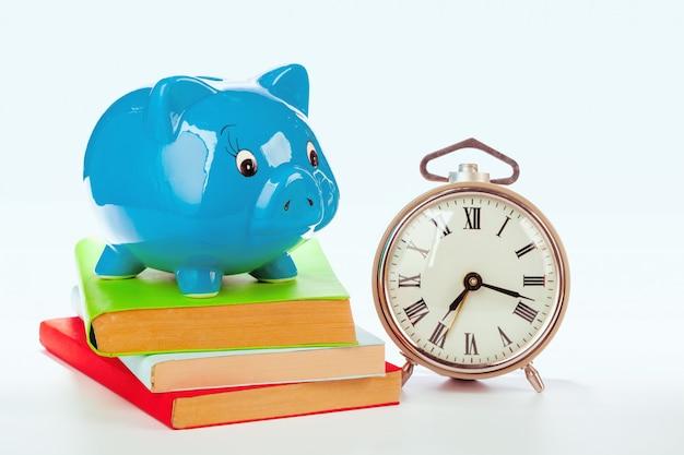 Hucha rosa con libros y reloj despertador