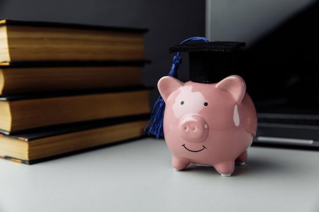 Hucha rosa con libros y sombrero. universidad, posgrado, concepto de educación.