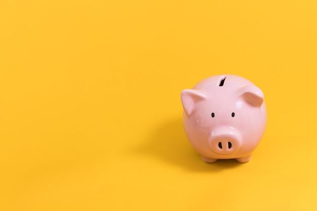 Hucha sobre fondo amarillo para economía, ahorro de dinero, riqueza y concepto financiero