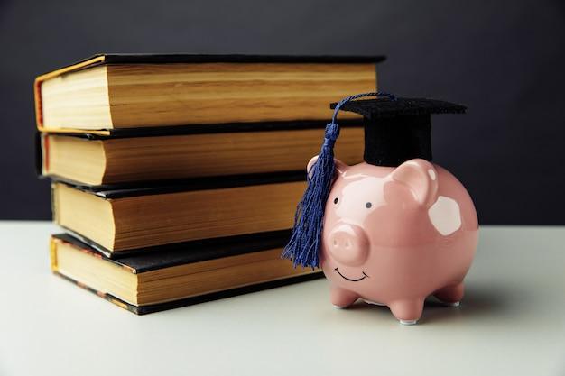 Hucha con sombrero con libros. universidad, posgrado, concepto de educación.