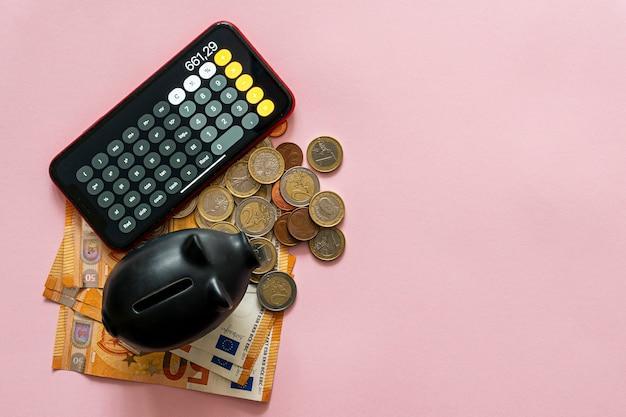 Hucha vacía con la cantidad de ahorro al lado sobre una mesa rosa. concepto de ahorro de dinero