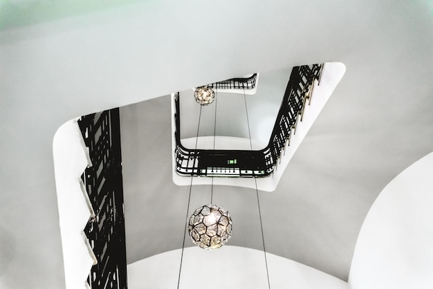 Hueco de una escalera interior de un edificio antiguo con paredes blancas y barandas negras.