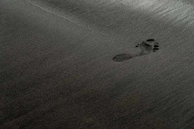 Huella en una fotografía de macro de playa de arena negra. rastro humano en una textura sedosa playa negra con poca profundidad de campo. fondo negro minimalista. tenerife voulcanic orilla arenosa.