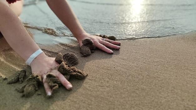 Huella de la mano en la arena junto al mar. fondo de verano
