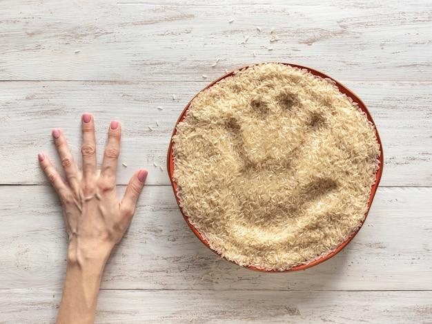 La huella de una mano en un plato de arroz crudo. vista superior.