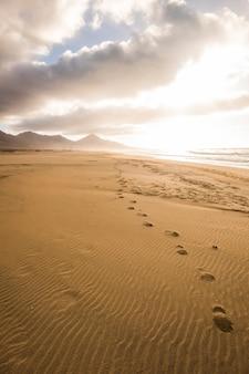Huella en la playa para explorar en concepto de lugar escénico salvaje durante las vacaciones de turismo alternativo