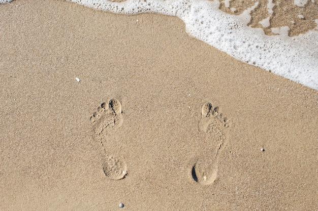 Huellas en la arena cerca del mar.