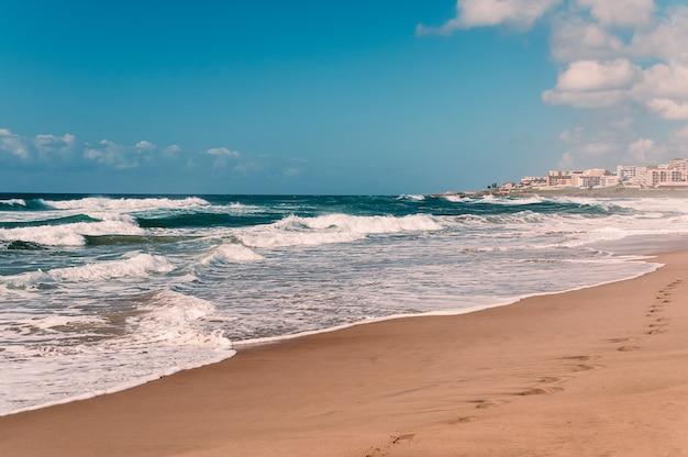 Huellas en la arena en la playa del océano, cielo azul, nubes blancas, arena amarilla,