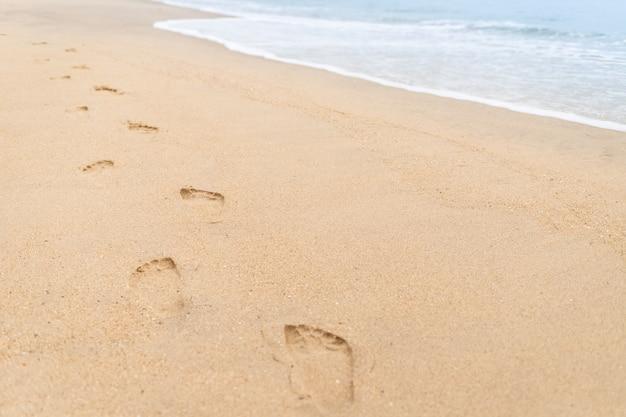 Huellas caminando por la playa y las olas.