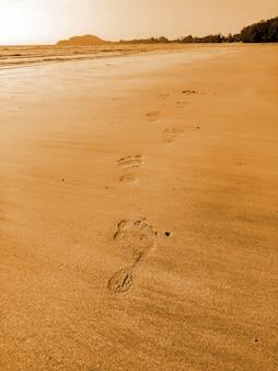 Las huellas del hombre en la playa de arena en vacaciones, tiempo de relax