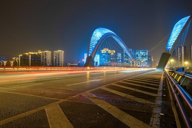 Huellas de luces y sombras de automóviles en puentes y carreteras por la noche