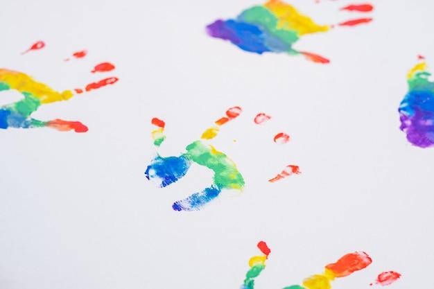 Huellas de las manos del niño de los colores del arco iris, en la hoja de papel blanco