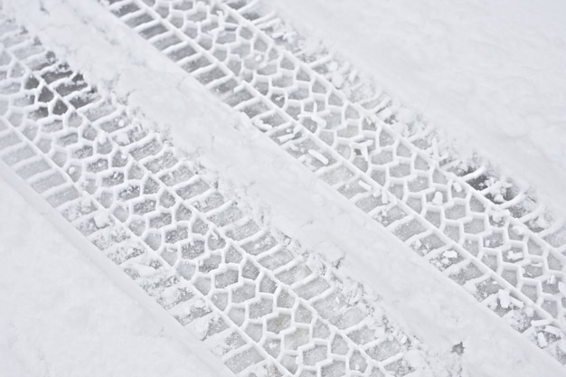 Huellas de neumáticos de coche en la nieve.