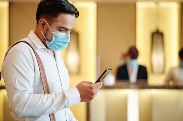 Huésped del hotel serio con máscara médica utilizando la aplicación móvil al pedir un taxi al aeropuerto